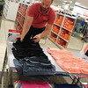 CATHY SPAULDING/Muskogee Phoenix<br /> Muskogee JCPenney General Manager Michael Anderson arranges clothes in preparation for Tax Free Weekend.