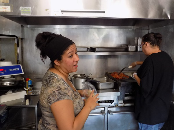 Staff photo by Mike Elswick<br /> Ashley Gossett, left, and Billie Jo Perkins are seen working in the kitchen of Taco Libres. Gossett, along with her husband Nathan, opened the restaurant last week on South Main Street.