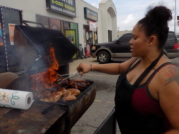 Staff photo by Mike Elswick<br /> Shannan Barnett, owner of The Oxtail, a pop-up restaurant, is seen at her smoker during a promotional event she cooked for at Boost Mobile on 32nd Street. Her smoker is filled with her jerk chicken leg quarters.