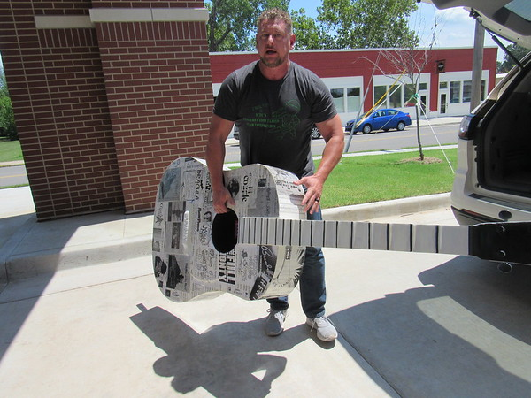 Shannon Barnes of Muskogee Area Arts Council carries a fiberglass guitar sculpture into Muskogee Little Theatre. Artist Nancy Wilkinson coated the guitar with old MLT programs.
