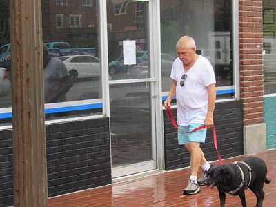CATHY SPAULDING/Muskogee Phoenix Midday showers on Friday don't keep Kenneth Satterwhite from walking his dog, Daisy, along Broadway. A little less than an inch of rain fell on Muskogee and Fort Gibson Friday morning, according to the AccuWeather website. Thunderstorms are expected Saturday.