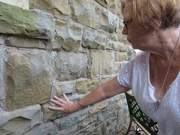 Staff photo by Cathy Spaulding<br /> Ann Rossi, chairwoman of Warner United Methodist trustees board, shows chipped mortar on the church's 114-year-old sanctuary. The<br /> church is raising money to replace the mortar.