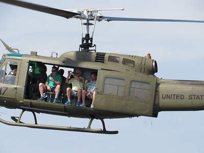 CATHY SPAULDING/Muskogee Phoenix A Huey helicopter carrying passengers, from left, Frank Godman, Jerry Cook and Andy Cook lands at Muskogee-Davis Regional Airport as part of the CAF Air Power History Tour.