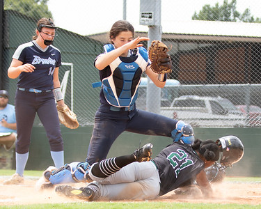 SHANE KEETER/Phoenix special photo Muskogee's Phynix Coleman, stuck in a rundown between third and home in Saturday's first game of two, slides and scores because of an overthrown ball from Bartlesville third baseman Allyson Tiller to catcher Maggie Largess, with ball.