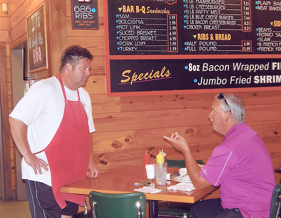 Kenny Greer checks in with a customer about his service at Mahylon's. He walks around his restaurant and visits with every individual he knows and makes sure his customers are satisfied.