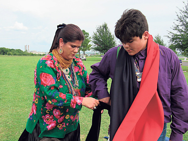 Amanda Proctor helps her son, Grayson Miller, put on his regalia before the Warriors for a Cure Powwow Gourd Dance. Miller was the powwow's junior head man.