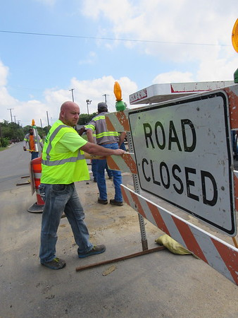 Staff photo by Cathy Spaulding<br /> Philip Flanary moves a sign near some street work on Okmulgee Avenue. As a city of Muskogee traffic supervisor, Flanary is responsible for keeping traffic signals and road markings up to date.