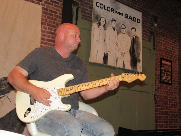 Staff photo by Cathy Spaulding<br /> Philip Flanary plays guitar next to an Oklahoma Music Hall of Fame picture of the group Color Me Badd. Flanary performed during the group's OMHOF induction.