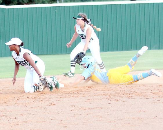 JOHN HASLER/Special to the Phoenix<br /> Oktaha's Karli Ashing slides in safely at second as the throw gets away from Muskogee's Jordan Simmons, left, and Hannah Cawthon, back during Oktaha's 1-0, eight-inning win on Monday.