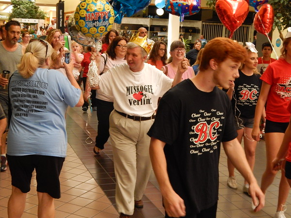 Staff photo by Mark Hughes<br /> Verlin Crigger acknowledges the cheering crowd as he is escorted by Bacone College cheerleaders through Arrowhead Mall on Saturday. Friends organized a community birthday party for him, and about 150 people attended.