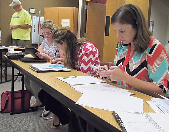 Staff photo by Cathy Spaulding<br /> New Fort Gibson certified staff members — from left, Autumn Keese, fifth-grade reading; Sara Hyde, middle school math, and Kristen Harrison, high school librarian — take notes during new staff orientation Friday.