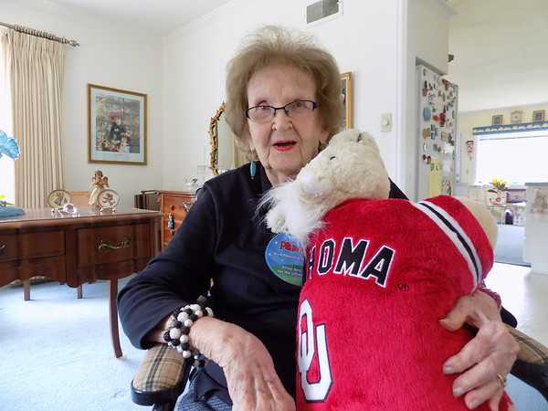 "Staff photo by Mike Elswick<br /> Katherine Lathim remains a hard-core University of Oklahoma Sooners fan and is seen with a stuffed animal wearing an OU sweater and also has a bright red OU watch. At nearly 100 years old she still watches every televised Sooners football game and will ""stay up to watch the last play, even its on 'til midnight."""