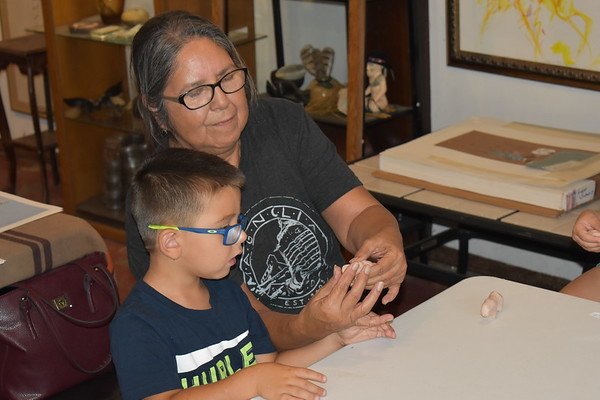 "Staff photo by Mark Hughes<br /> Jenelle Washington shows her 3-year-old great-grandson, Easton Landrum, how to shape the buffalo's head while in sculpting class at the Legacy Cultural Learning Community. She brought her great-grandson to get him interested in art and Muscogee (Creek) Nation culture,  because ""they may be gifted, who knows?"""