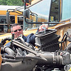 LEFT: Muskogee Public Schools Transportation Director Brad Smythe sprays ether into a school bus engine to help it start.