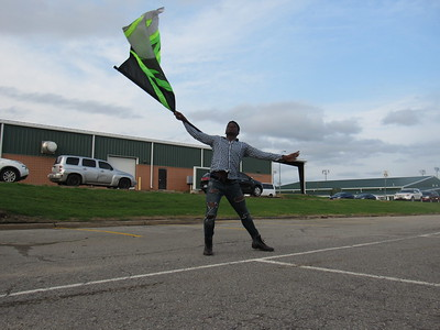 CATHY SPAULDING/Muskogee Phoenix Muskogee High School student Troy Buckhanan swings a green and black flag while practicing for the MHS color guard. He practiced Tuesday night at the same time as the MHS band. Buckhanan said he has been practicing his flag work for the Muskogee High School color guard for the past year. He said he has learned respect, loyalty and dedication by being part of the 17-member group.