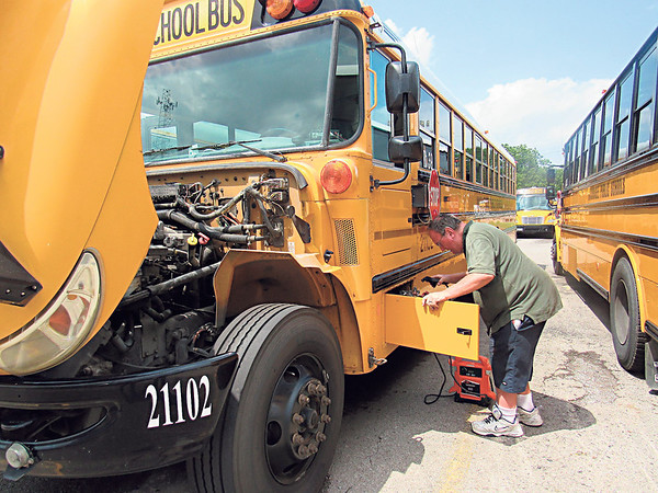 CATHY SPAULDING/Muskogee Phoenix ABOVE: Muskogee Public Schools Transportation Department mechanic Billy Turner charges a school bus battery Wednesday afternoon. Transportation officials spent Wednesday getting buses ready for the kickoff of the new school year, which begins today.
