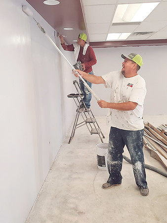CHESLEY OXENDINE/Muskogee Phoenix<br /> (from left to right) Painters Tino Majano and Martin Garza apply a coat of paint to the rebuilt interior of Webbers Falls Public Schools' main building.