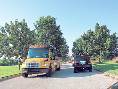 CATHY SPAULDING/Muskogee Phoenix School buses and parents' vehicles pass each other on the Seventh and Eighth Grade Academy's long driveway. Seventh- and eighth-graders moved from Alice Robertson Junior High School to the former Ben Franklin Science Academy this year. Story on Page 4.