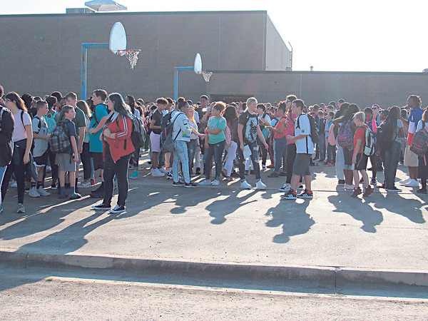 CATHY SPAULDING/Muskogee Phoenix<br /> Students hang around outside the Seventh and Eighth Grade Academy, awaiting the start of a new school year, Thursday.
