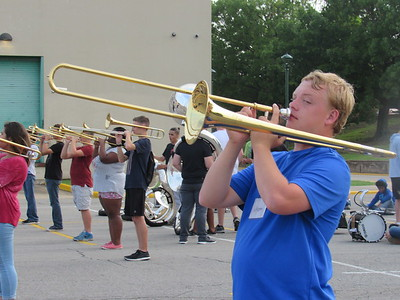 CATHY SPAULDING/Muskogee Phoenix Muskogee High School band member Wyatt Walker holds his trombone high as he waits to start marching during a Tuesday night drill.