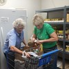 Staff photo by Cathy Spaulding<br /> Community Food Pantry volunteers Deborah Carment, left and Flora Cox, fill a shopping cart with food for a needy person. The Community Food Pantry originally was part of Muskogee Cooperative Ministries.