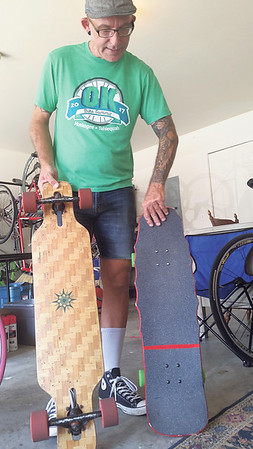 Staff photo by Cathy Spaulding<br /> Ronald Milligan holds a couple of the skateboards he likes to ride. He said his family shares his love of skateboarding and cycling.
