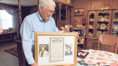 Charles McGrew proudly shows off the wall hanging he has in his home that shows him in the U.S. Navy, his wife Mary Louise and their marriage certificate. They have been married for 73 years.