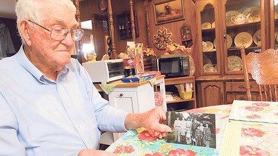 Charles McGrew of Warner holds a photo of his family that was taken in California. McGrew calls himself an Okie because he and his family moved to California from Oklahoma during the Dust Bowl. McGrew is at the far left in the photo at 16 years old. A World War II veteran, McGrew will celebrate his 96th birthday on Saturday.