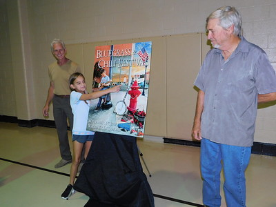 KENTON BROOKS/Muskogee Phoenix  Lexie Applegate, 8, points to herself on the newly unveiled poster for the 40th annual Bluegrass and Chili Festival in Wagoner. Poster artist Doug Henderson, right, and Mayor A.J. Jones look on. Another Wagoner child, Cohen Harris, also is on the poster. The poster was unveiled Tuesday in a ceremony at the Wagoner Civic Center. The festival is scheduled for Sept. 6-7.