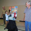 KENTON BROOKS/Muskogee Phoenix <br /> Lexie Applegate, 8, points to herself on the newly unveiled poster for the 40th annual Bluegrass and Chili Festival in Wagoner. Poster artist Doug Henderson, right, and Mayor A.J. Jones look on. Another Wagoner child, Cohen Harris, also is on the poster. The poster was unveiled Tuesday in a ceremony at the Wagoner Civic Center. The festival is scheduled for Sept. 6-7.