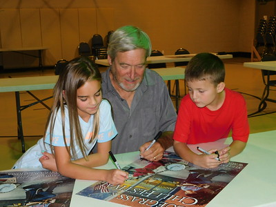 Artist Doug Henderson, center, and Wagoner children Lexie Applegate, left, and Cohen Harris sign posters Tuesday after the unveiling of the poster for this year's Bluegrass and Chili Festival. Henderson has designed 20 posters for the festival and he incorporated the two children in the poster for the first  time this year. This year's festival is scheduled for Sept. 6-7.