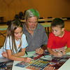 Artist Doug Henderson, center, and Wagoner children Lexie<br /> Applegate, left, and Cohen Harris sign posters Tuesday after<br /> the unveiling of the poster for this year's Bluegrass and Chili<br /> Festival. Henderson has designed 20 posters for the festival<br /> and he incorporated the two children in the poster for the first<br />  time this year. This year's festival is scheduled for Sept. 6-7.