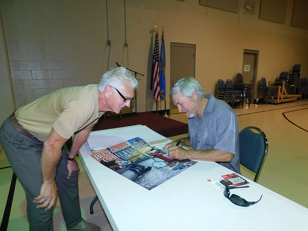 KENTON BROOKS/Muskogee Phoenix<br /> Wagoner Mayor A.J. Jones, left, watches as artist Doug Henderson signs a copy of the poster he created for the 40th annual Bluegrass and Chili Festival. An unveiling was held Tuesday at the Wagoner Civic Center. Henderson has designed poster for 20 of the festivals. This year's festival is scheduled for Sept. 6-7.