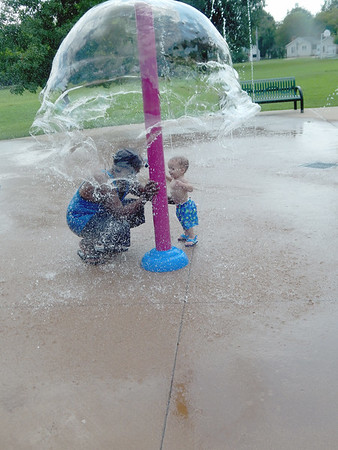 "KENTON BROOKS/Muskogee Phoenix<br /> Bobby Johnson holds his grandson Jordan during a pause in the spraying of water at the Rotary Park splash pad on Tuesday. The elder Johnson said ""I'm the papa"" to Jordan, who turns 1 on Sunday. The Johnsons, along with Bobby's wife Tammy, took advantage of the weather to enjoy the splash pad."