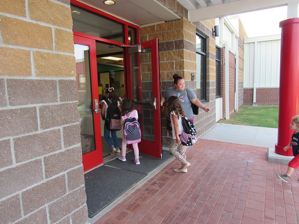 CATHY SPAULDING/Muskogee Phoenix Hilldale parent Amy Yelle holds Hilldale Elementary School's front door open for children on the first day of school. The Hilldale Education Foundation sold bricks laid in the front entrance.