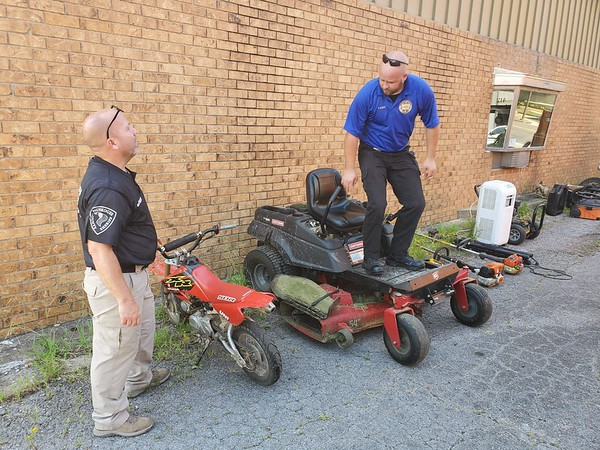 CHESLEY OXENDINE/Muskogee Phoenix<br /> Lt. Perry Galvin (left) joins Deputy Tyler Lowe in recording an inventory of stolen goods recovered from a Taft Road property Tuesday, including a zero-turn lawnmower.