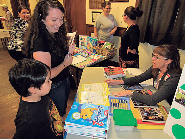 Staff photo by Cathy Spaulding<br /> Juliana Cruz, left, and her 7-year-old son, James, look over homeschool books and materials shown by Jennifer Havenar during a Homeschool 101 information meeting sponsored by the Tahlequah Homeschool Group. Cruz began homeschooling her two children about six months ago.