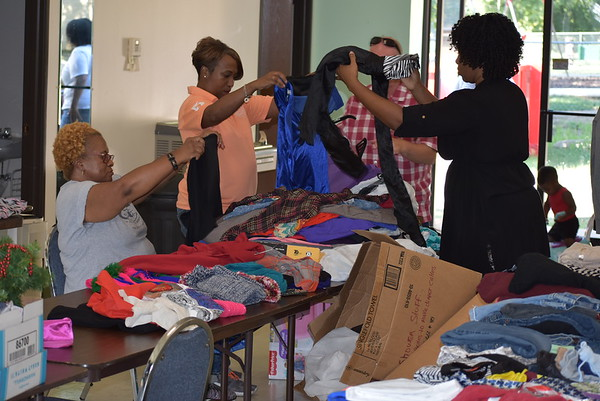 Staff photo by Mark Hughes<br /> Sundra Wiley-Everly, Deneese Goodman and Stacey Edwards sort clothes at the Praise Center Family Church in preparation of the church's giveaway from 9 a.m. to noon Saturday. There will be free clothes, school supplies, household items, jewelry and purses.The church is located at 302 N. Seventh St.