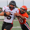 Phoenix special photo by Shane Keeter<br /> Tahlequah's Braxton Stopp drags down Hilldale quarterback Dawson  Neighbors in Thursday's preseason scrimmage.
