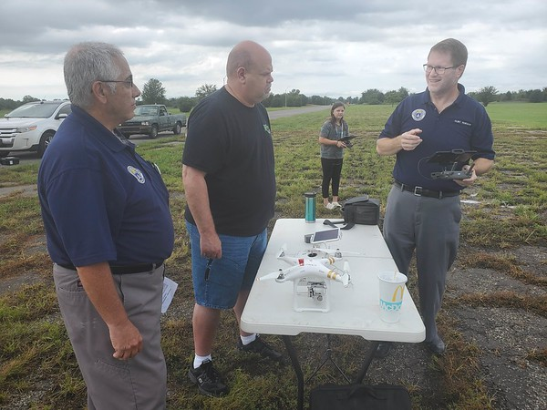 CHESLEY OXENDINE/Muskogee Phoenix Muskogee Nighthawk Squadron Civil Air Patrol members Jason Unwin (left) and Clinton Morgan (right) give Paul Watts a lesson on drone usage during a demonstration event Saturday morning.