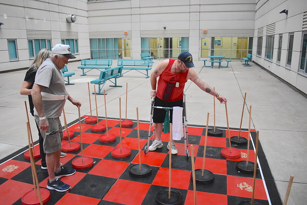 Staff photo by Mark Hughes<br /> Army veteran Bill Huffhines watches as his opponent, Shawn Messers, Marine Corps, moves his red checker during a game of checkers in the third floor atrium at Jack C. Montgomery VA Medical Center. The checkerboard is 12 feet by 12 feet and was an Eagle Scout project by Kellen Hamilton. The checkers are made out of five-gallon bucket lids.