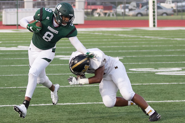 Phoenix special photo by Shane Keeter<br /> Muskogee's Quintevin Cherry, left, pushes away Midwest City's Jacob Reed during Friday's game on Creek Nation Field at Indian Bowl. The Roughers lost 26-20.