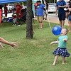 Staff photo by Mark Hughes<br /> Rachel Lewis tosses the ball to her 2-year-old daughter, Sydney, during Saturday's River Rumba Regatta at Three Forks Harbor. While not watching the races, attendees turned the regatta into a family event. Three inflatable waterslides were available at the regatta for the first time for children to enjoy.