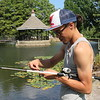 CATHY SPAULDING/Muskogee Phoenix<br /> Aarron Clayborn baits his fishing hook while fishing Monday afternoon.
