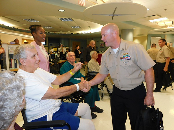 Gary Gardener, left, shakes hands with Chief Petty Officer selectee Eugene Ilang after Ilang and 41 other sailors sang to Gardener and other veterans Tuesday at the Inpatient Rehabilitation Unit on the fifth floor of the Jack C. Montgomery Medical Center. Gardener is a U.S. Navy veteran, and the sailors came from Tinker Air Force Base in Oklahoma City.