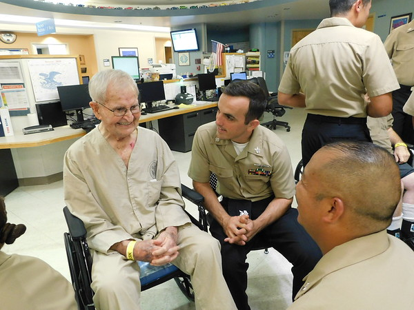 Vance Brinsfield, left, a 93-year-old U.S. Army veteran, tells stories about fighting at the Battle of the Bulge to Chief Petty Officer selectees Marcus Gass and David Nguyen. Gass, Nguyen and 40 other sailors sang to veterans at the Jack C. Montgomery VA Medical Center.