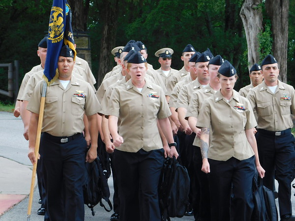 KENTON BROOKS/Muskogee Phoenix<br /> Sailors from Tinker Air Force Base in Oklahoma City march toward the entrance of the Jack C. Montgomery VA Medical Center on Tuesday before going to the center's fifth floor and Inpatient Rehabilitation Unit to sing for veterans there.