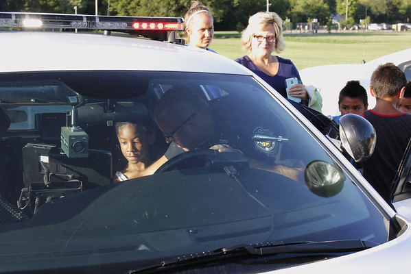 Staff photo by Harrison Grimwood<br /> Pancho, also known as Muskogee Police Officer Danny Spears, shows Keon Tottress, 9, the inner workings of a police cruiser at Robison Park during Okies Neighborhood Night Out.