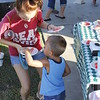 Staff photo by Harrison Grimwood<br /> Kelsey Jameson, left, helps her son Bryson Noyes, 4, get a piece of watermelon at Robison Park on Tuesday night during Okies Neighborhood Night Out.