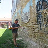 CATHY SPAULDING/Muskogee Phoenix<br /> Matt Pruegert of Dirt Work Done Right sprays compressed air between bricks of a downtown Muskogee building Thursday afternoon.